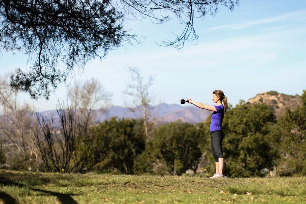 Kettlebell swings performed by a woman in an open outdoor field
