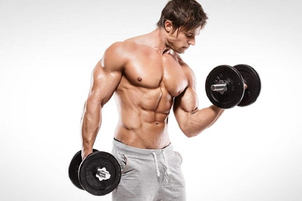 Man holding a pair of dumbbells while lifting the other one close to his chest