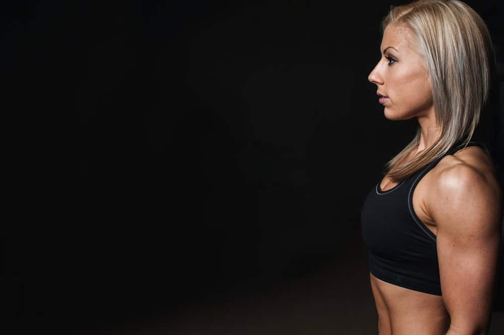 Woman standing sideways while wearing a black sports bra