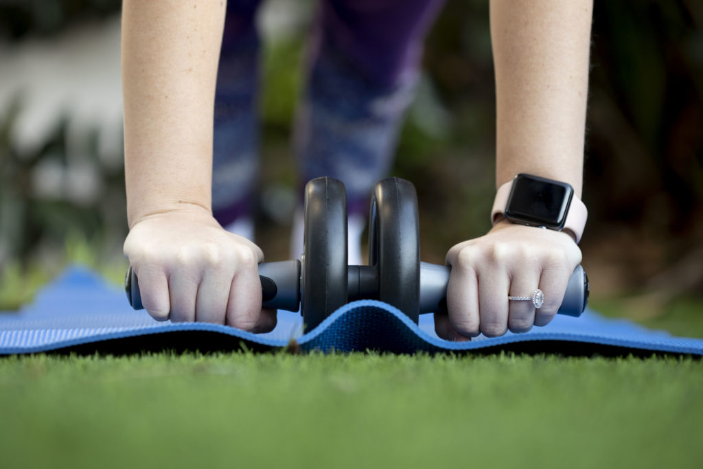 Person using an ab roller with a blue yoga mat in their lawn