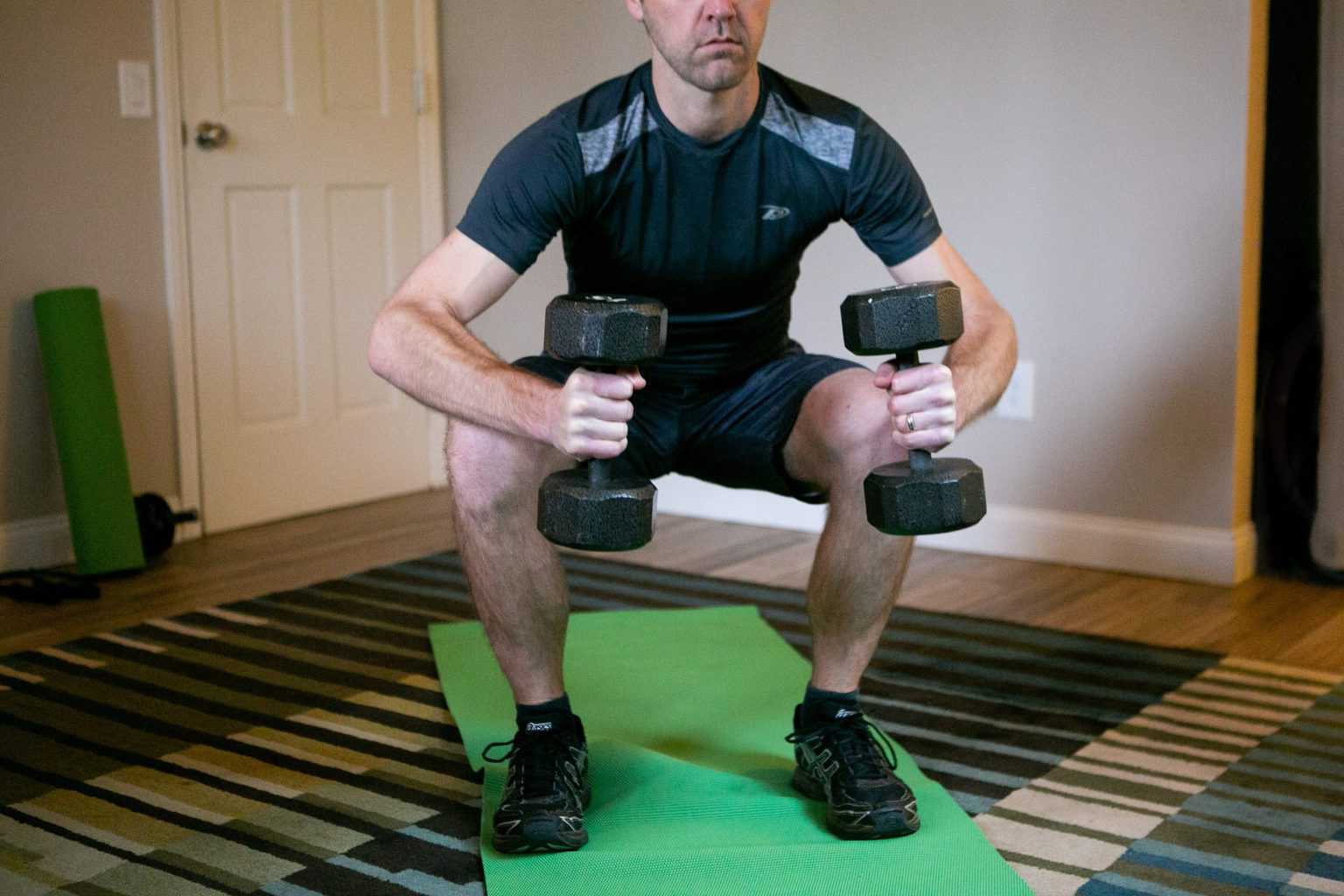 Man doing dumbbell squats while holding dumbbells with each hand