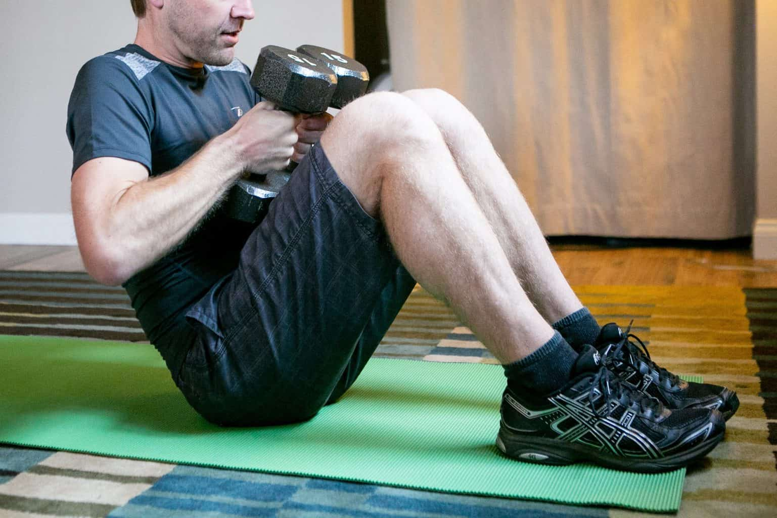 Man sitting down on the floor while holding dumbbells with each hand