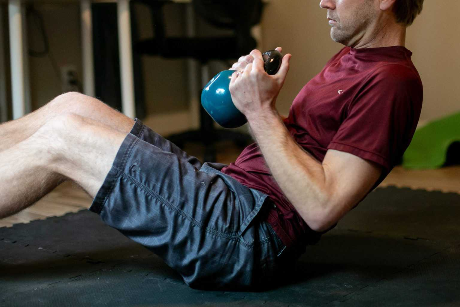 Man doing crunches while holding a kettlebell with both hands