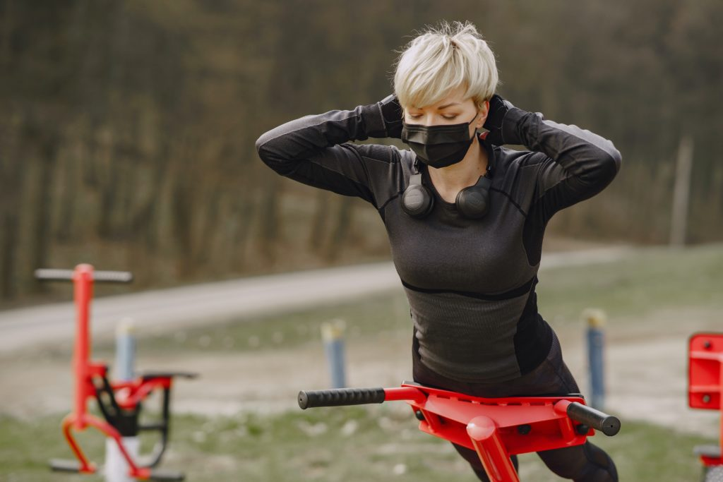 Woman wearing a mask doing exercises outdoors while using a Roman Chair