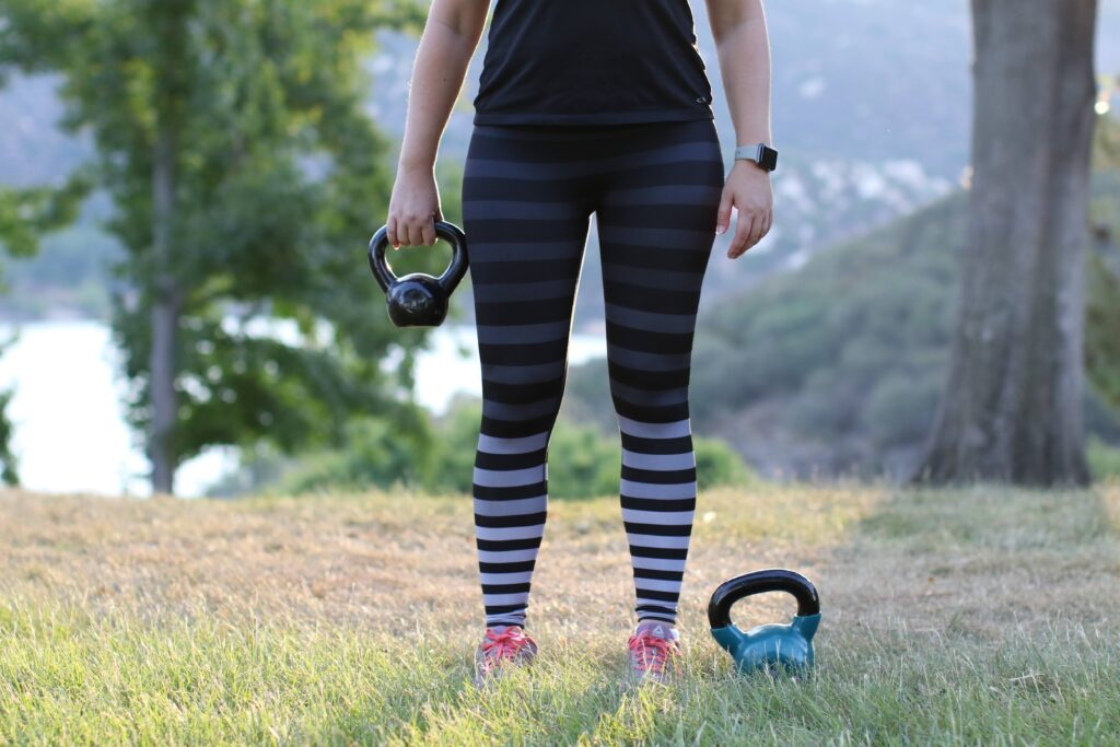 Woman holding a kettlebell with one hand, while another one is placed on the grass
