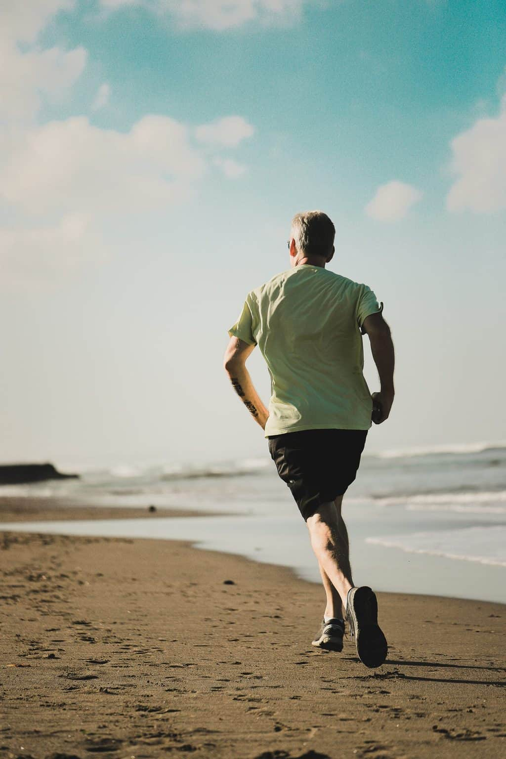 An old man jogging on the beach